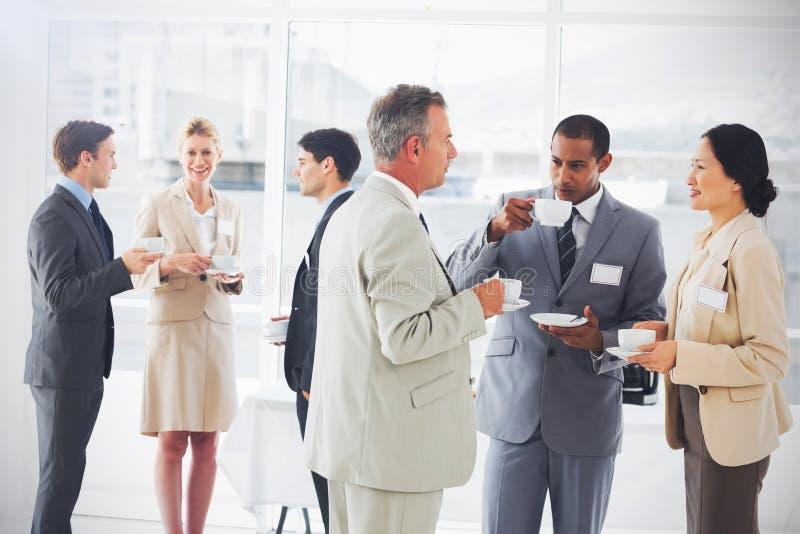 商人聊天的和饮用的咖啡在会议 库存例证
