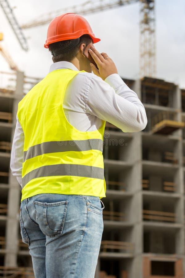 商人背面图在安全帽的和安全由p授予谈话 免版税图库摄影