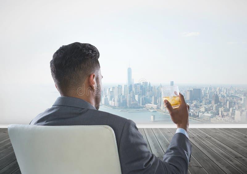 商人背面图坐拿着杯酒精的椅子,当看城市时 图库摄影