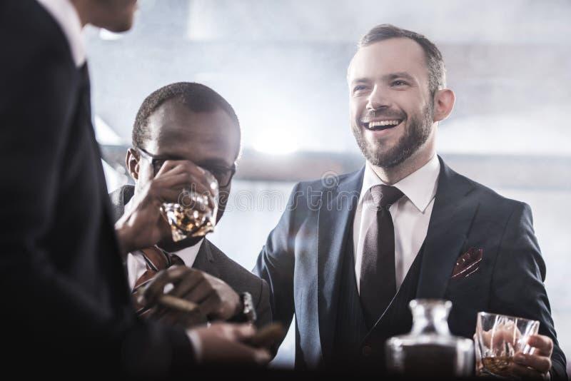 商人花费时间一起喝威士忌酒和抽烟的不同种族的小组 免版税图库摄影