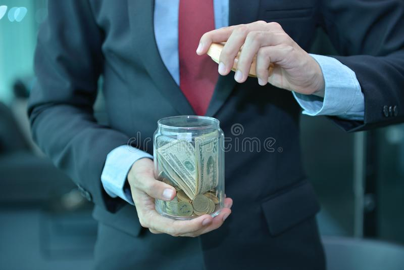 商人藏品和挽救在一个木瓶子的金钱钞票 免版税库存照片