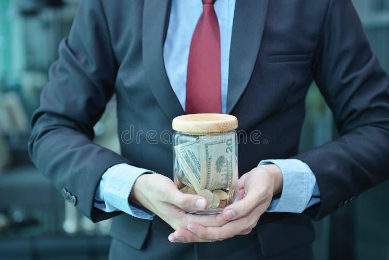 商人藏品和挽救在一个木瓶子的金钱钞票 库存图片
