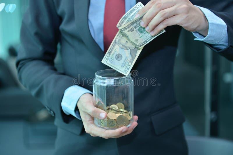 商人藏品和挽救在一个木瓶子的金钱钞票 图库摄影