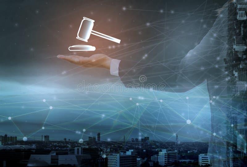 商人藏品锤子象和信息关于网上拍卖,都市风景背景,概念互联网的未来派手  免版税库存图片