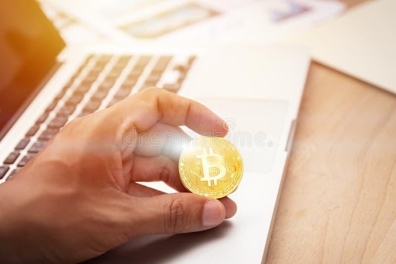 商人藏品cryptocurrency金黄bitcoin硬币在手中与在背景的计算机膝上型计算机 隐藏货币, 库存图片