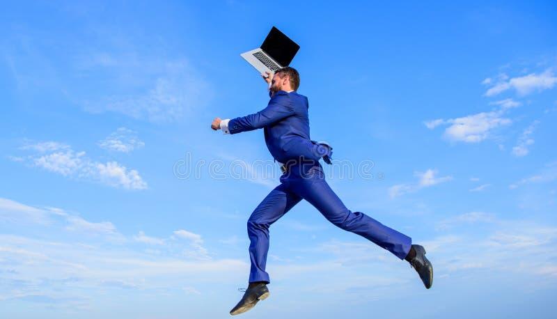 商人被启发的企业家感觉强有力去改造世界 人被启发拿着上面膝上型计算机,当跃迁时 免版税库存图片