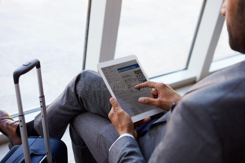 商人观察登舱牌在机场休息室 免版税库存图片