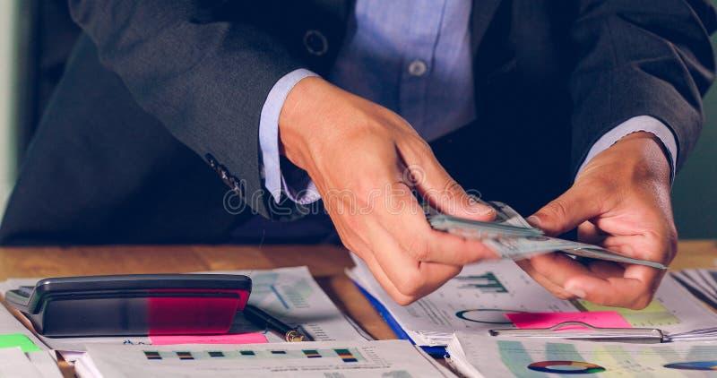 商人计数金钱和计划财务项目的和用途计算器分析财政项目的文件和的图表的 免版税库存图片