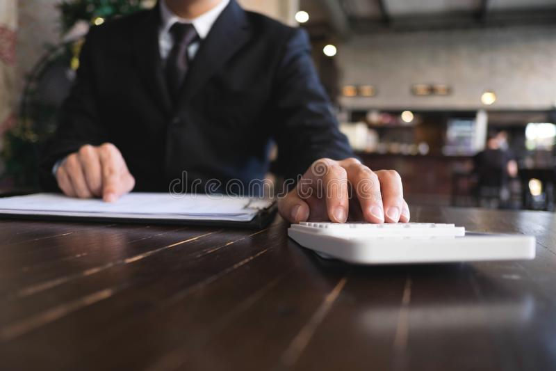 商人计算从出口业务的收入在木桌上 E 免版税库存照片