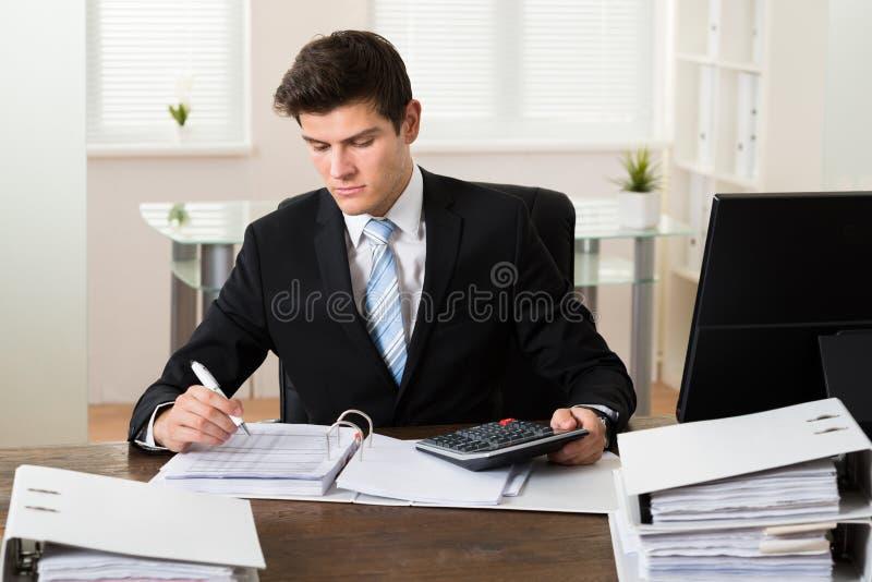 商人计算的税在办公室 库存图片