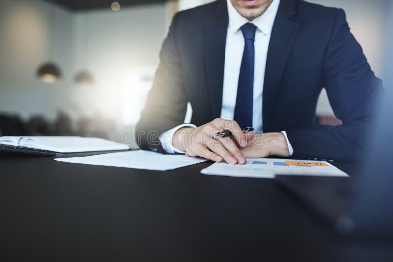 商人读书文书工作,当坐在他的办公桌时 免版税库存照片