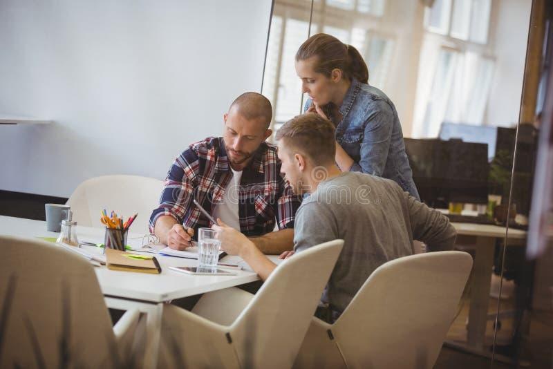 商人谈论与同事在会议期间 免版税库存照片