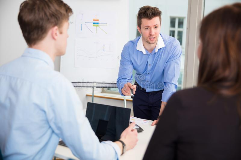 商人谈论与同事在办公室 免版税库存照片
