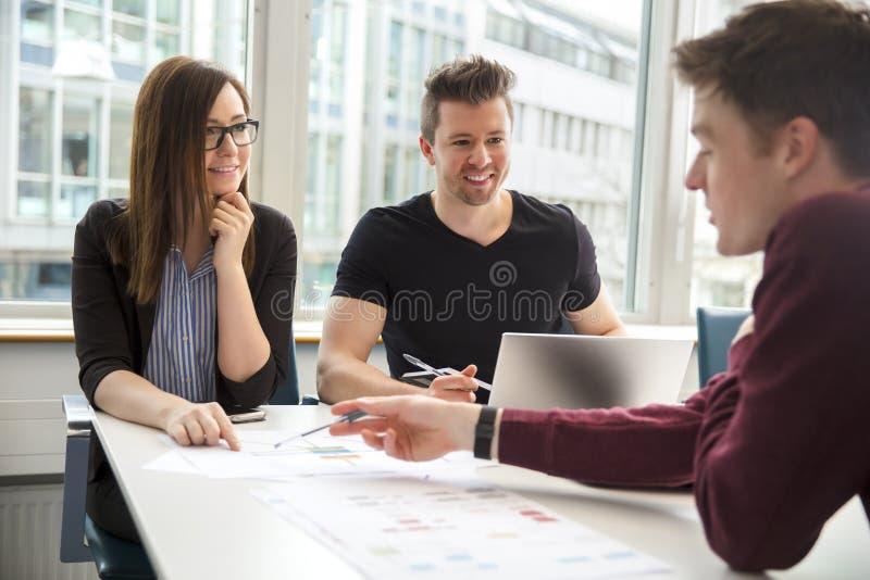 商人谈论在文件在办公室 库存图片