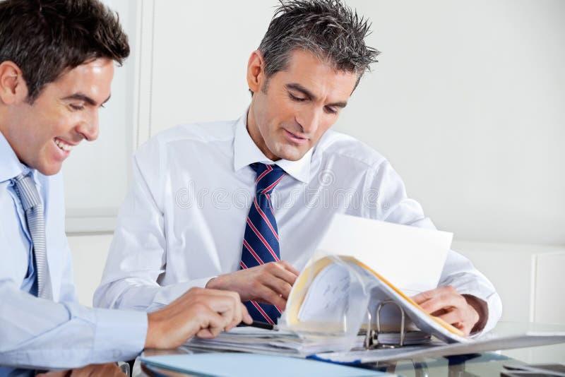 商人谈论文书工作在办公室 免版税库存图片