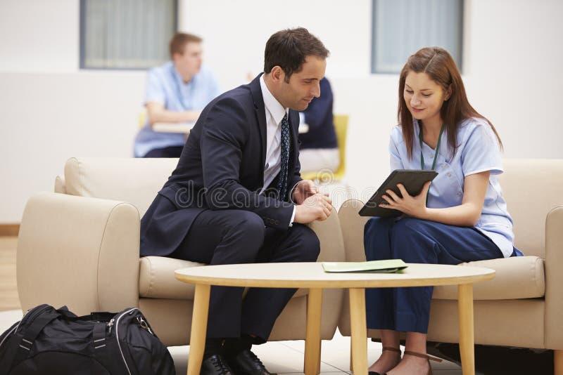 商人谈论结果与数字式片剂的护士 图库摄影