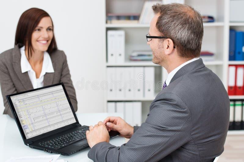 商人谈话与一个同事在办公室 免版税库存图片