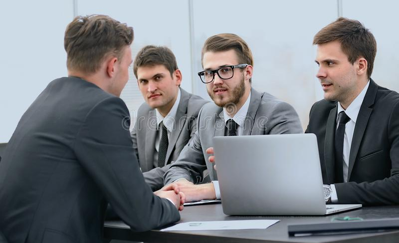 商人谈话与企业队在书桌 免版税库存照片