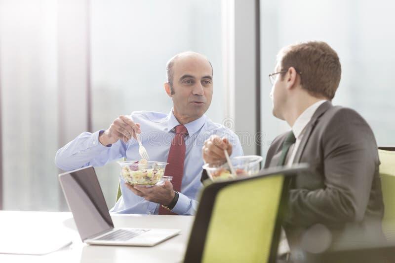 商人谈话与同事,当吃午餐在会议室里在见面期间在办公室时 图库摄影