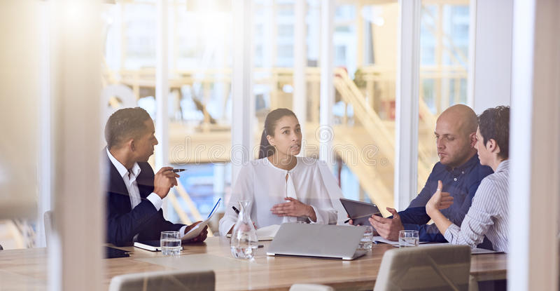 商人谈话在会议期间在现代办公室 免版税图库摄影