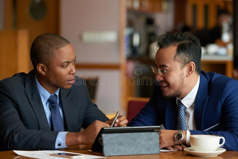 商人谈话在咖啡馆桌上 库存图片