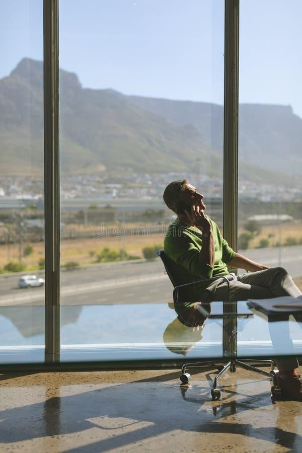 商人谈话在手机在办公室 库存图片