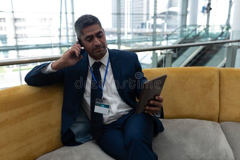 商人谈话在手机,当使用数字片剂在办公室大厅时 库存图片
