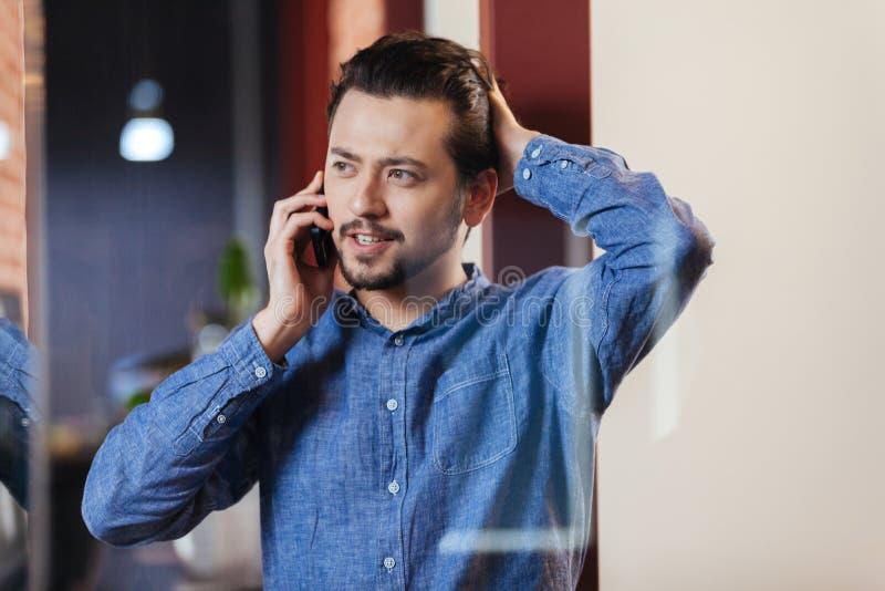 商人谈话在电话在办公室 图库摄影