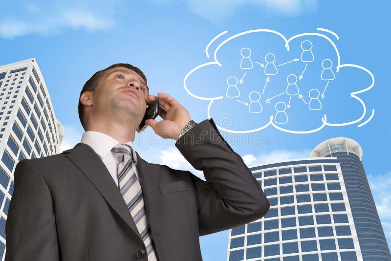 商人谈话在电话 云彩与 库存图片