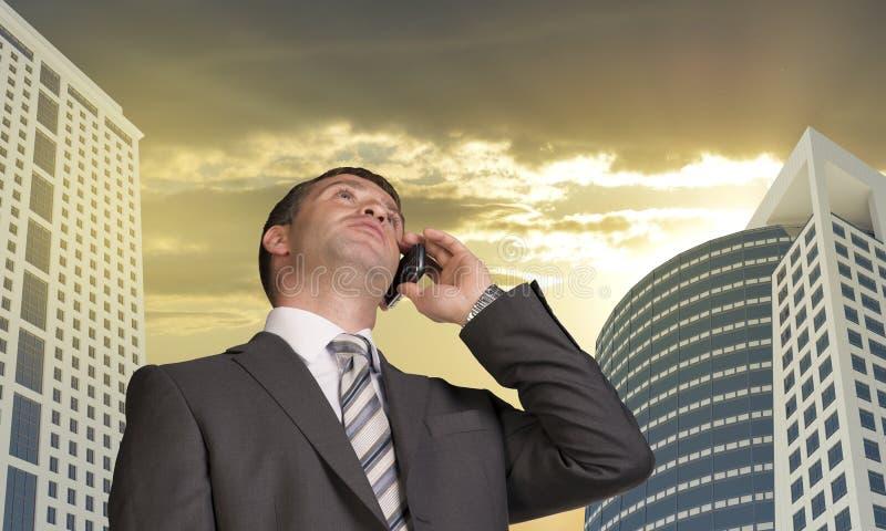商人谈话在电话 摩天大楼和 库存图片