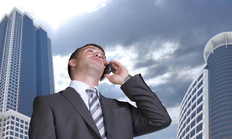 商人谈话在电话 摩天大楼和 图库摄影