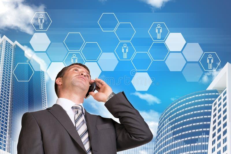 商人谈话在电话 摩天大楼和 免版税库存照片