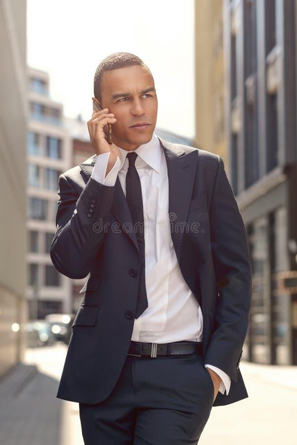 年轻商人谈话在街道的电话 库存照片