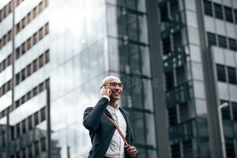 商人谈话在走的手机户外 库存照片