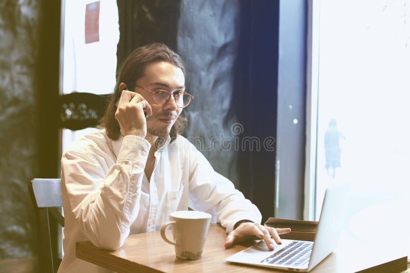 商人谈话由有被打开的膝上型计算机的手机在咖啡馆,共同工作的空间 有咖啡断裂 免版税库存图片