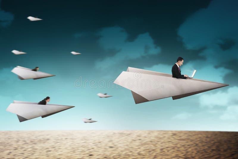 商人赛跑与去为更好的事业的纸飞机 库存图片
