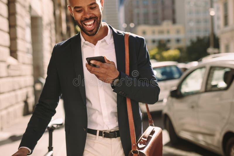 商人走与他的自行车和谈话在电话 图库摄影