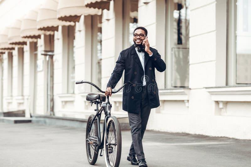 商人走与自行车和谈话在电话 免版税库存照片