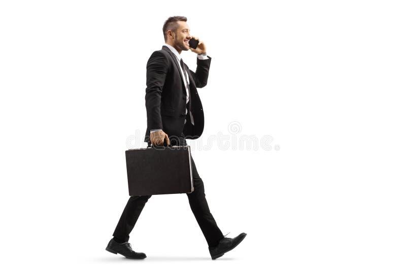 商人走和谈话在一个手机 图库摄影