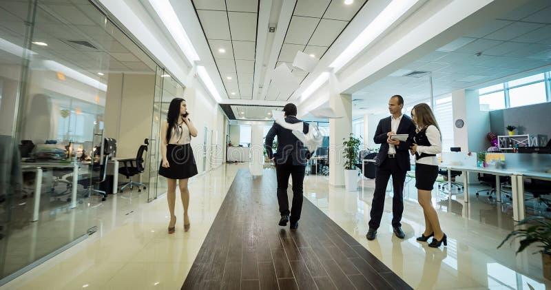 商人走在办公室走廊的,商人C 库存图片