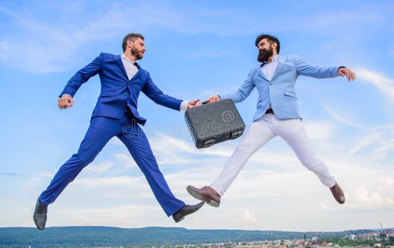 商人跳飞行空中,当举行公文包时 与培养的案件您的事务 之间成功的交易 库存照片