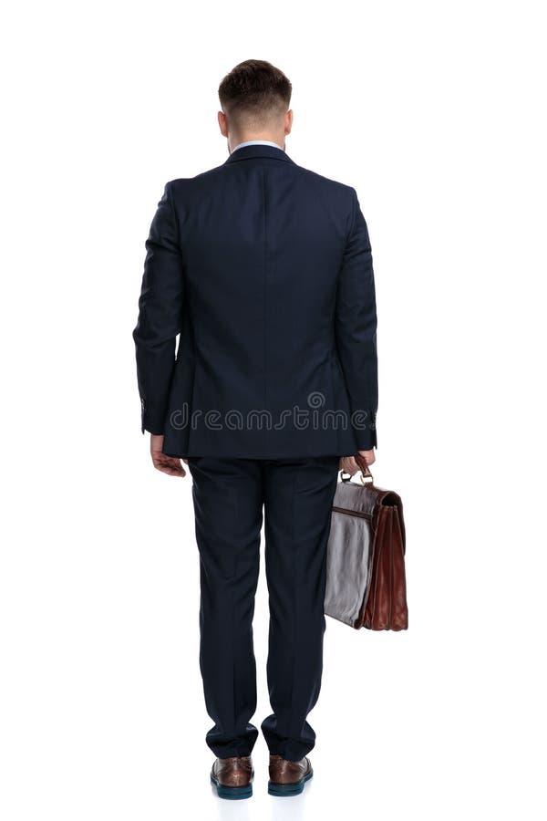 商人身分和拿着他的公文包的背面图 免版税图库摄影