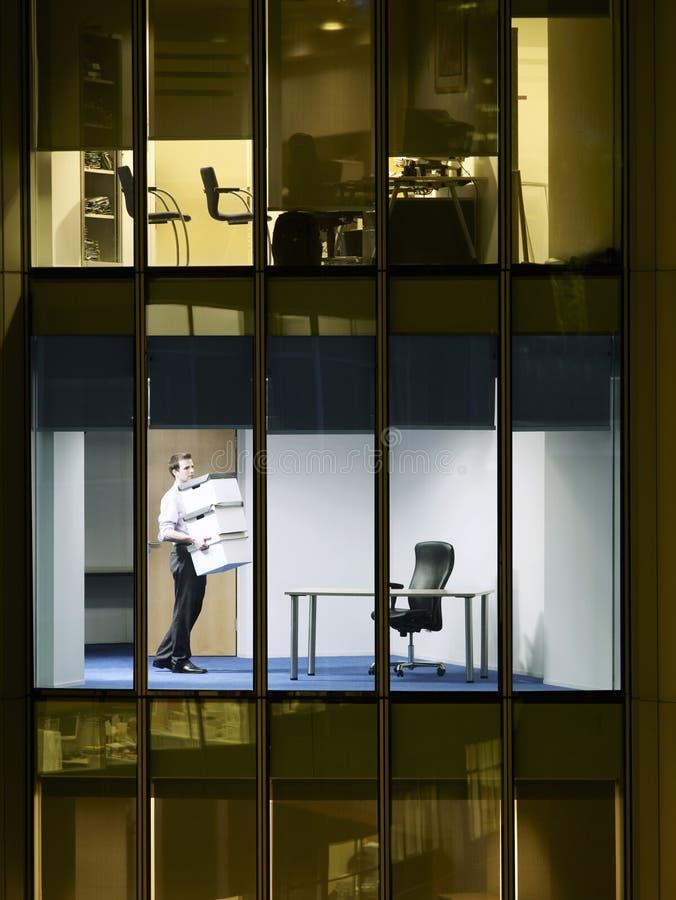 商人运载的堆箱子在办公室 图库摄影