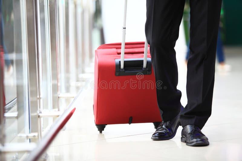 商人运载的手提箱特写镜头,当走通过乘客搭乘桥梁时 免版税库存照片