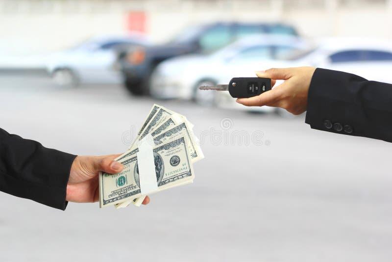 商人递了金钱给举行在手汽车钥匙的女实业家或女推销员,汽车业,汽车贸易,汽车的贷款 库存图片
