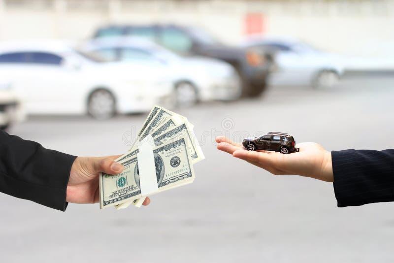 商人递了金钱给拿着微型汽车模型,汽车业,汽车贸易,汽车的贷款的女实业家或女推销员 免版税库存照片
