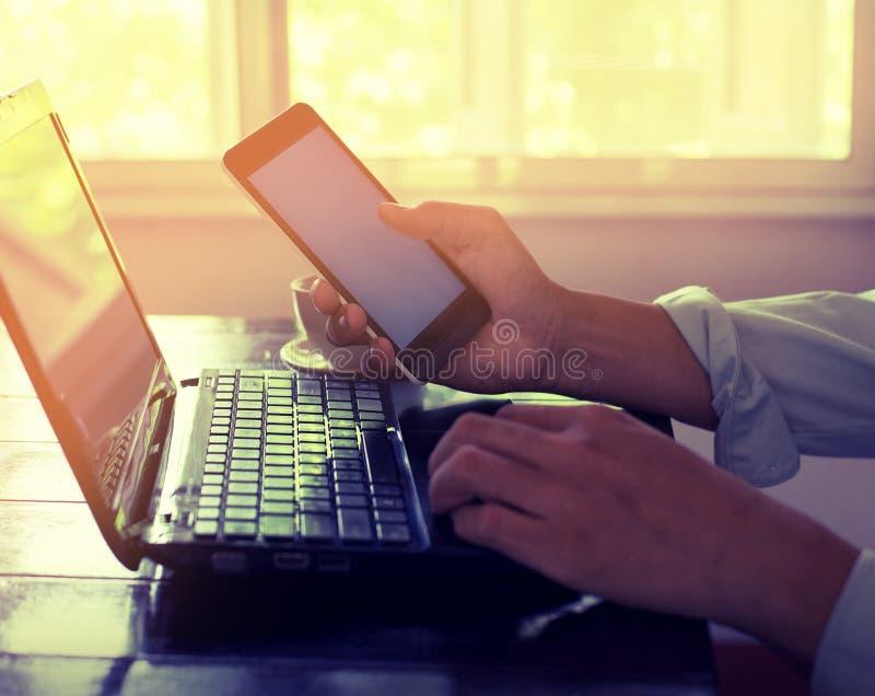 年轻商人递繁忙研究他的膝上型计算机和使用坐巧妙的电话在木桌上 免版税图库摄影