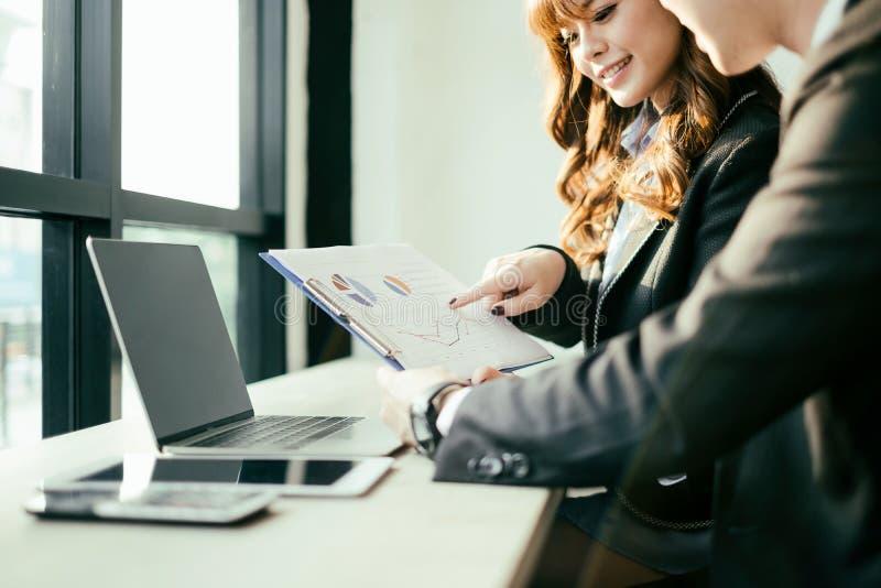 商人遇见激发灵感和谈论项目与膝上型计算机和手机,配合概念 免版税库存图片