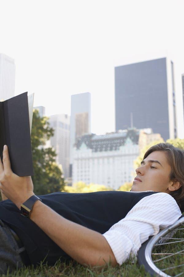 商人阅读书在城市公园 免版税库存图片