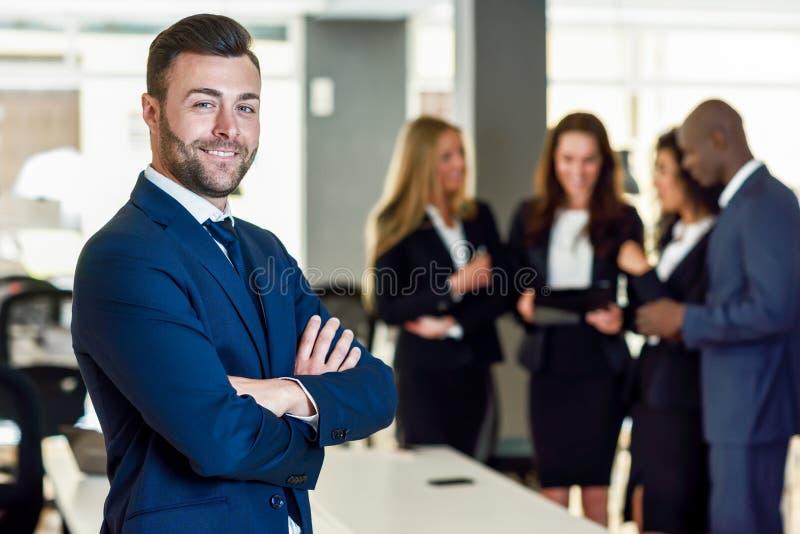 商人领导在有买卖人工作的现代办公室 免版税图库摄影